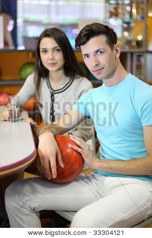 Beautiful brunette woman and man sit at table in bowling; girl holds glass with pure water and man holds red ball; focus on man; shallow depth of field