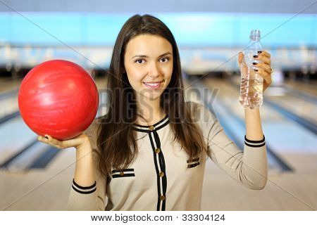 Young brunette woman holds red ball and bottle with water in bowling club; shallow depth of field