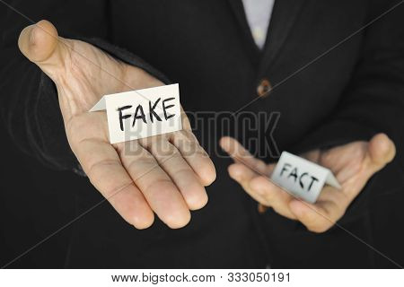 A Piece Of Paper With The Inscription Fake In A Mans Hand On The Background Of Another Hand With The