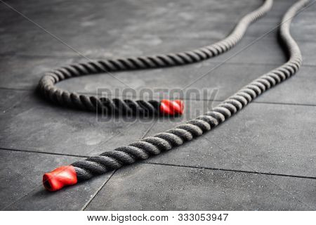Close Up Of Fitness Battle Ropes Lie On Black Floor In Fitness Gym. Sport And Fitness Equipment. Fun