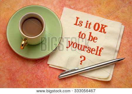 Is it OK to be yourself? A question on a napkin with a cup of coffee. Conformism, nonconformism, being different and individuality concept.
