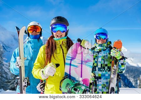 Picture of happy sports woman and men with skis and snowboard standing at ski resort