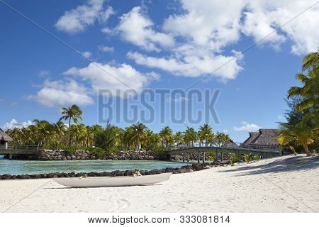 White Traditional Polynesian Boat On A Sandy Beach, A Bridge Across The Sea Strait To The Shore With