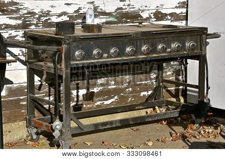 An Old Neglected Propane Grill Left Outside Unused And Uncared For,