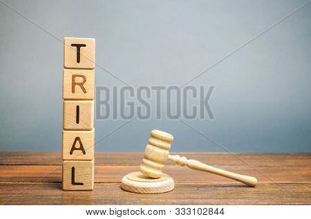 Wooden Blocks With The Word Trial And Hammer Of A Judge. Settlement Of Disputes And Consideration Of