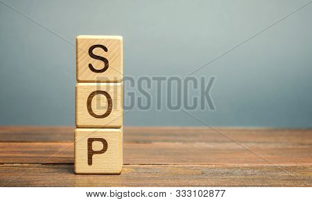 Wooden Blocks With The Word Sop ( Standard Operating Procedure ). Instructions To Assist Employees I