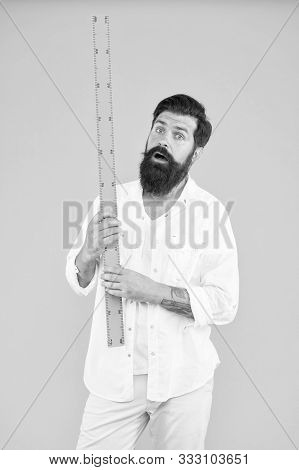 Measuring Length At Geometry. Bearded Man Holding Ruler For Geometry Lesson On Yellow Background. Un