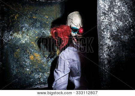 Portrait Of A Scary Clown Peering From Behind A Wall. Halloween Mask Of Fear. Clown Horror Poster