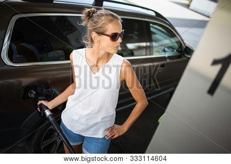 Car pumping gas at gas pump. Closeup of man pumping gasoline fuel in car at gas station.