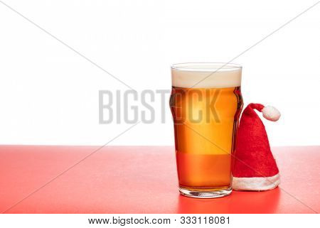 Full pint glass of lager beer or ale with Santa Claus red hat on red isolated on white background