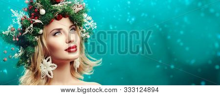 Christmas winter beauty girl. Beautiful happy young woman with a Christmas pine wreath on her head, decorated with Christmas balls, berries and snowflakes.  Studio portrait over xmas green background