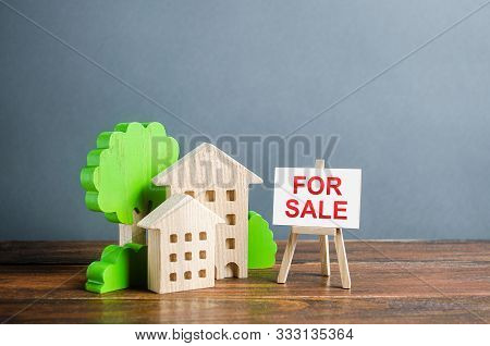 Figures Of Houses And An Easel Sign For Sale. Buying And Selling Real Estate, Hot Offers And Propert