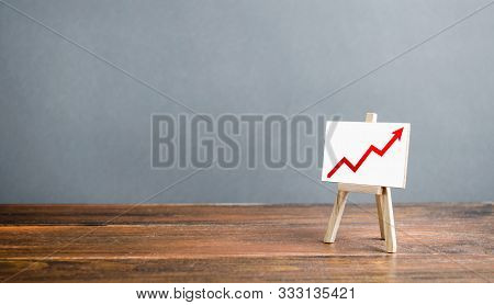 Easel With A Red Arrow Up. The Concept Of Success, Rapid Growth And Development. Business Planning A