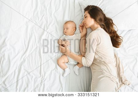 Co-sleeping With Infants. Millennial Mother Embracing Her Cute Little Baby During Sleep, Top View