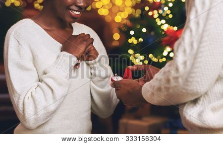 Christmas Proposal. Unrecognizable African American Man Giving Engagement Ring To His Excited Girlfr