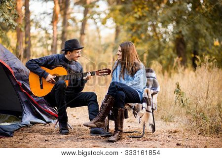 Portrait Of Young Couple Sitting On Camp Chair With Guitar Near Camp Tent. Time Together In Harmony