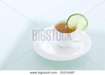Tasse Tee mit Limette auf einer Glasoberfläche
