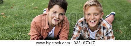 Panoramic Shot Of Two Cheerful Brothers Lying On Green Grass And Smiling At Camera