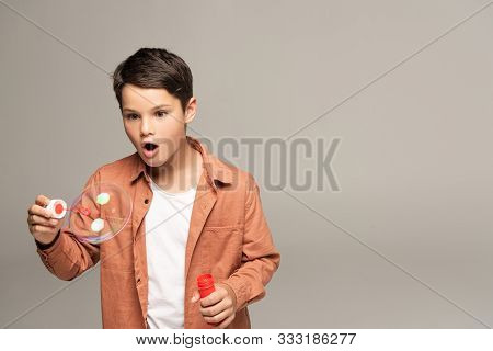 Amazed Boy Looking At Soap Bubble Isolated On Grey