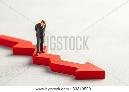 Figurine Of A Businessman In A Suit And Tie And A Red Down Arrow. The Concept Of Bankruptcy, Falling