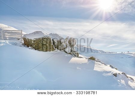 Scenic Alpine Mountain Peak Covered With Thick Snow Layer With Rocks And Fence Defense From Avalanch