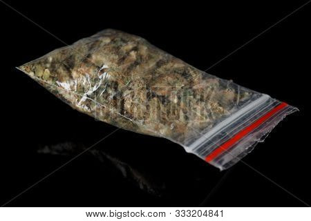 Dime bag with cannabis buds isolated on black background