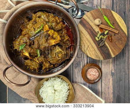 Overhead View Of Spicy Goat Curry, Mutton Curry, Nihari, Rogan Josh In A Bowl With Chapati And Plain