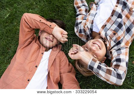 Top View Of Two Cheerful Brothers Covering Eyes With Hands While Lying On Green Grass