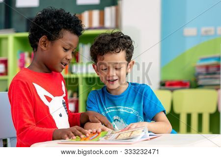 Student In International Preschool Reading A Magazine Book Together In School Library, Education, Ki