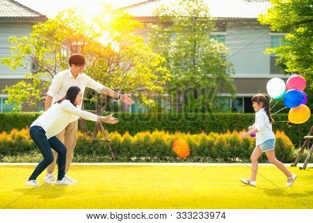 Asian Daughter Running To Mother And Father, She Enjoyed The Play Balloons, This Concept Can Use For