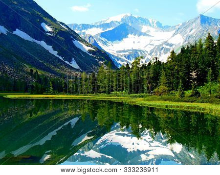 View Of Mountains Near Lake With Reflection In Water. Dramatic Peaceful Scene. Snow Mountains In Spr