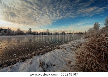 The Clouds Gather Over The Freezing River On A Winter Morning At The Northern Finland. There Are Spi
