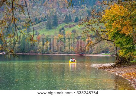 Tourists Go For A Canoe Trip Around The Lake Bohinj On A Beautiful Day In Autumn. Travelers Kayak To