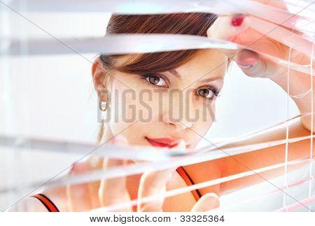 Beautiful woman is looking through jalousie