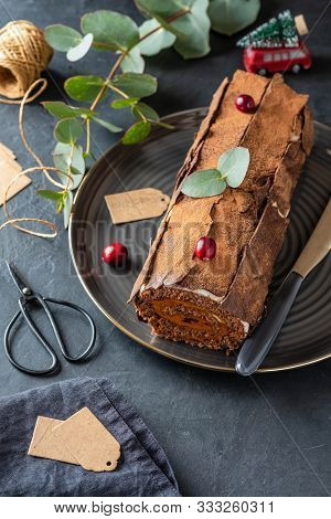 Buche De Noel. Traditional Christmas Dessert, Christmas Yule Log Cake With Chocolate Cream, Cranberr