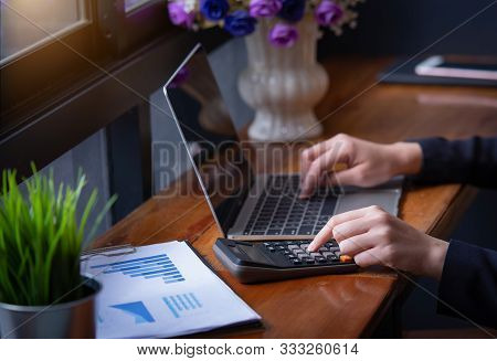 Businesswoman Hand Pressing On Calculator For Calculating Numbers With Laptop. Hand Press Button Use