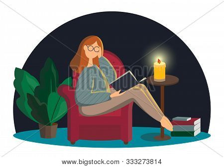 Cute Redhead Lady In Glasses Sitting In Comfy Armchair And Reading Book. Adorable Young Woman Spendi