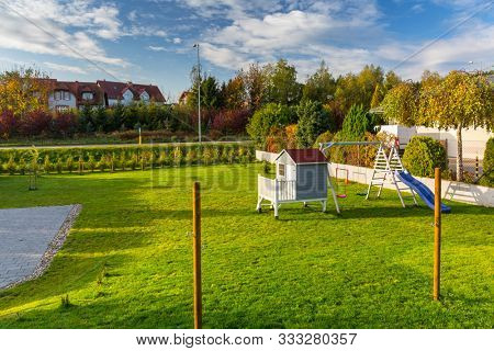 Green garden iwith beautiful wooden house for children and playground at autumn.