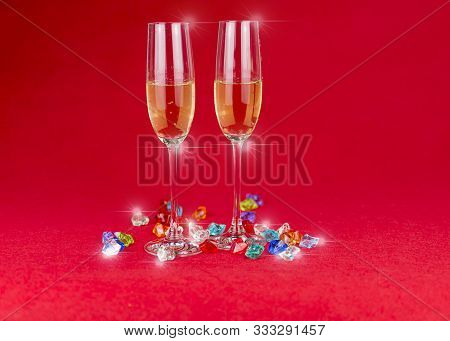 Glasses Of Champagne On Red Background And Sparkling Crystal Stones On Base Ant Foreground. New Year