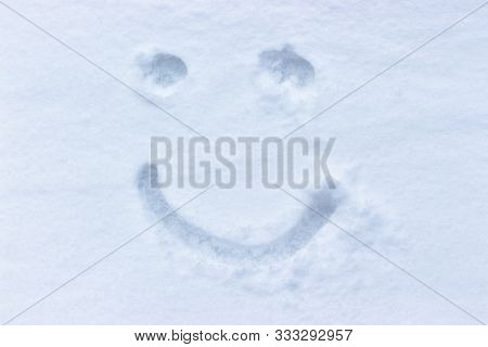 Smiley Drawing In The Snow. Woman In The Fresh, Untouched Snow. Graza And Smile, Emoji. Pure White F
