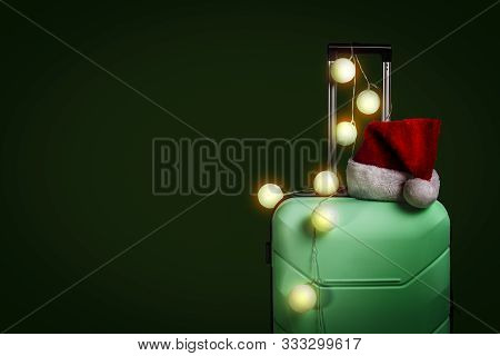 Plastic Suitcase, Santa Claus Cap And Garland On A Dark Green Background. Concept Of Travel, Busines