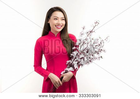 Beautiful Asian Woman Wearing Vietnam Traditional Ao Dai Holding Peach Flower In Tet Holidays.