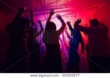 Team. A Crowd Of People In Silhouette Raises Their Hands On Dancefloor On Neon Light Background. Nig