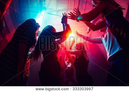 Until Sunrise. A Crowd Of People In Silhouette Raises Their Hands On Dancefloor On Neon Light Backgr