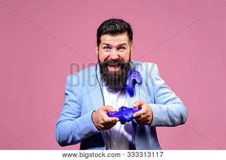 poster of Smiling bearded man using video-game controller. Businessman with joystick. Guy playing on console. Handsome man with game controller playing video games. Gamer man with gamepad playing in video game