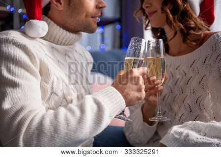 Cropped View Of Boyfriend And Girlfriend In Sweaters Clinking With Champagne Glasses At Christmastim