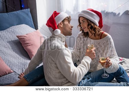 Boyfriend And Girlfriend In Santa Hats Holding Champagne Glasses At Christmastime