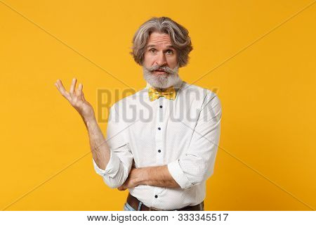 Perplexed Elderly Gray-haired Mustache Bearded Man In White Shirt Bow Tie Posing Isolated On Yellow