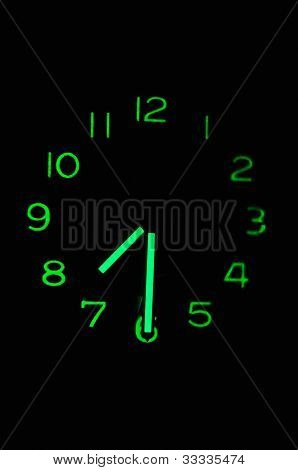 phosphorescent clock on black background