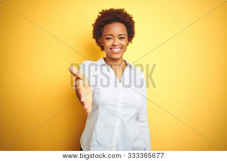 African american business woman over isolated yellow background smiling friendly offering handshake as greeting and welcoming. Successful business.